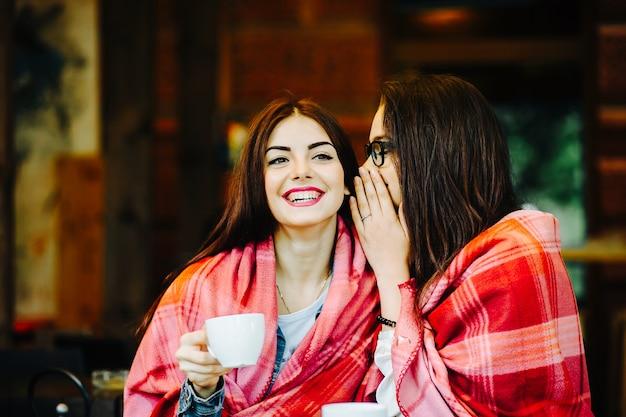 Deux jeunes et belles filles bavardant sur la terrasse avec une tasse de café