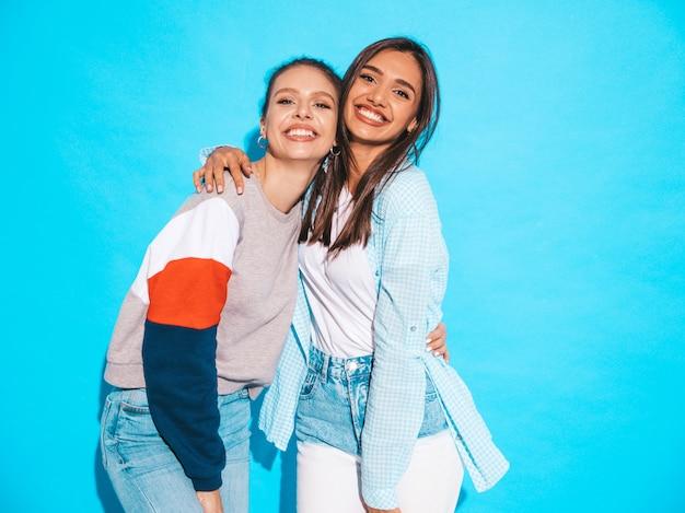 Deux jeunes belles filles blondes blondes souriantes dans des vêtements de t-shirt coloré d'été à la mode. femmes insouciantes sexy posant près du mur bleu. modèles positifs s'amusant