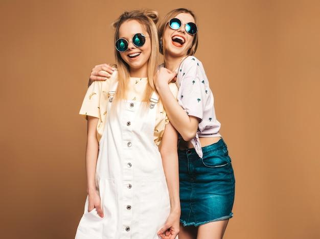 Deux jeunes belles filles blondes blondes souriantes dans des vêtements de t-shirt coloré d'été à la mode.