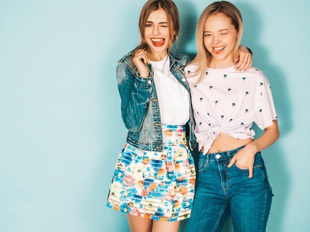 Deux jeunes belles filles blondes hipster blond souriant dans des vêtements colorés d'été à la mode.