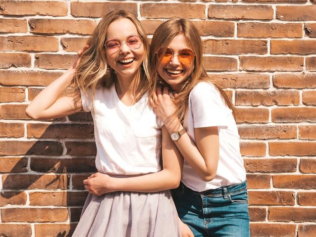 Deux jeunes belles filles blondes souriantes hipster en vêtements de t-shirt blanc à la mode d'été. . modèles positifs s'amusant avec des lunettes de soleil