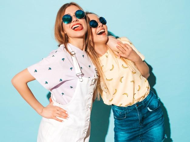 Deux jeunes belles filles hipster blondes souriantes en jeans d'été à la mode jupent les vêtements.