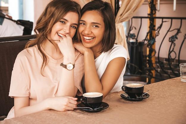 Deux jeunes belles filles hipster souriantes dans des vêtements décontractés d'été à la mode.des femmes sans soucis discutant dans la terrasse d'un café terrasse et buvant du café.des modèles positifs s'amusent et communiquent