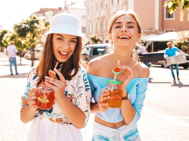 Deux jeunes belles filles hipster souriantes dans des vêtements d'été à la mode et un chapeau panama.
