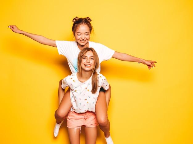 Deux jeunes belles filles hipster souriantes dans des vêtements d'été à la mode. sexy femmes insouciantes posant près du mur jaune.modèle assis sur le dos de son amie et levant les mains