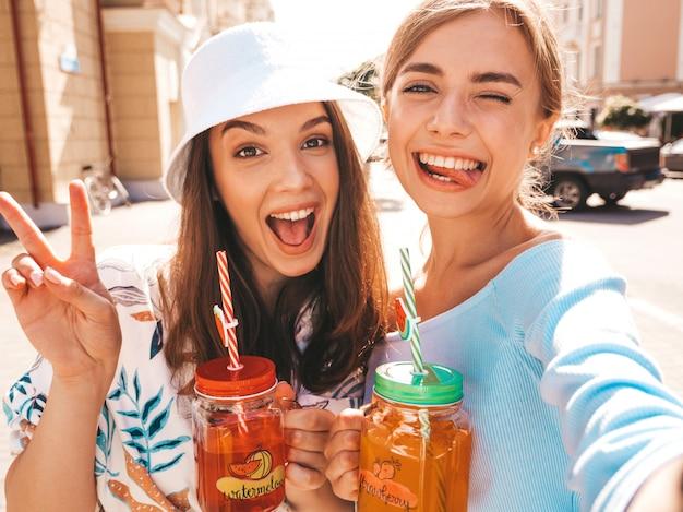 Deux jeunes belles filles hipster souriantes dans des vêtements d'été à la mode