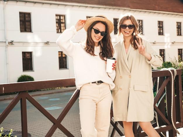 Deux jeunes belles filles hipster souriantes en pull et manteau blancs à la mode