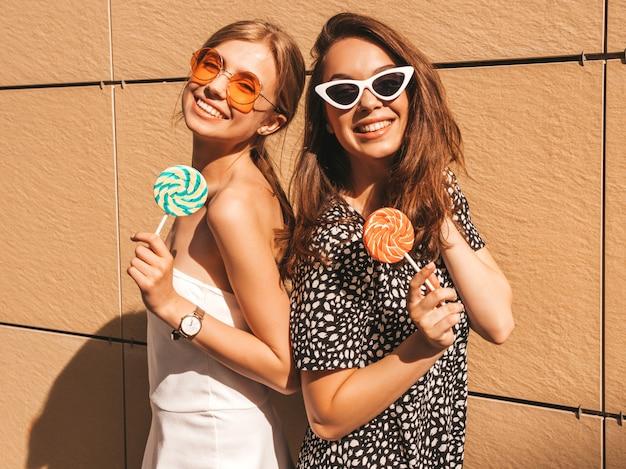 Deux jeunes belles filles hipster souriantes en robe d'été à la mode.