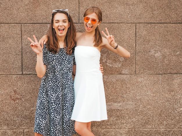 Deux jeunes belles filles hipster souriantes en robes d'été à la mode.