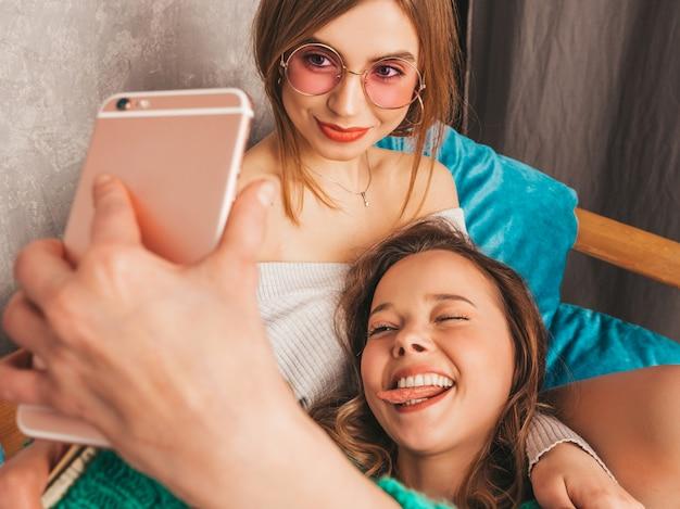 Deux jeunes belles filles magnifiques souriantes dans des vêtements d'été à la mode. femmes insouciantes sexy posant à l'intérieur et prenant selfie. modèles positifs s'amusant avec smartphone.