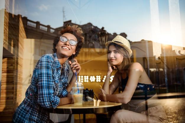 Deux jeunes belles filles souriant, parlant, se reposant au café. tiré de l'extérieur.