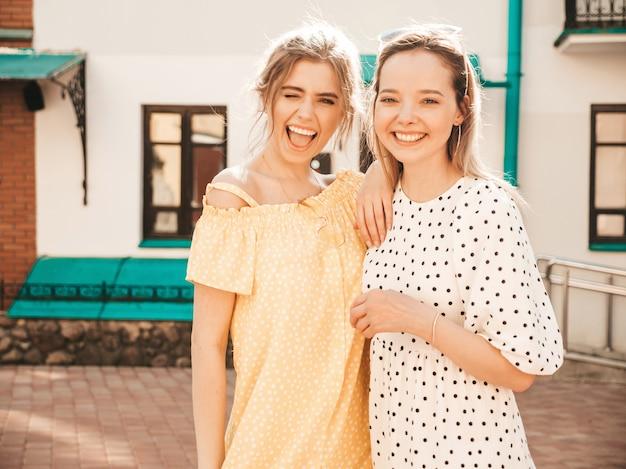Deux jeunes belles filles souriantes hipster en robe d'été à la mode. femmes insouciantes sexy posant sur fond de rue en lunettes de soleil. modèles positifs s'amusant et étreignant