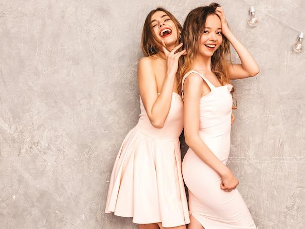 Deux jeunes belles filles souriantes en robes rose pâle d'été à la mode. femmes insouciantes sexy posant. modèles positifs s'amusant