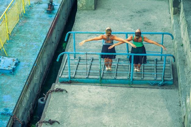Deux jeunes belles sœurs jumelles dansent le ballet dans la ville avec un costume de ballet. danse de synchronisation urbaine. danse de rue industrielle. avec effet spécial. pose synchronisée. chaussures et robe de ballet de pointe.
