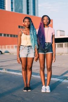 Deux jeunes belles sœurs noires se tenant la main en écoutant de la musique posant