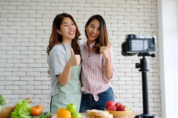 Deux jeunes blogueurs asiatiques en train de parler en enregistrant des vidéos, concept vlog