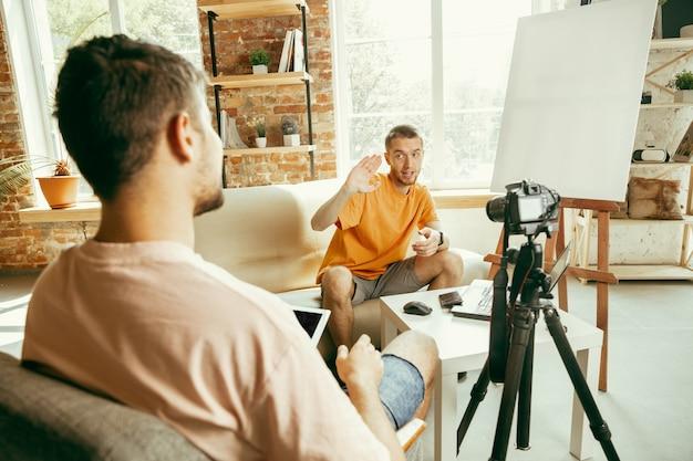 Deux jeunes blogueurs masculins de race blanche dans des vêtements décontractés avec un équipement professionnel ou une caméra d'enregistrement vidéo interview à la maison