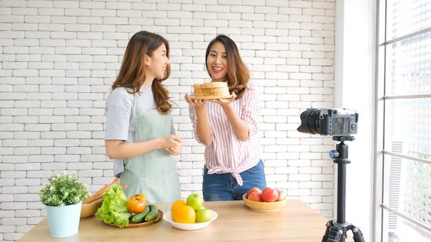 Deux jeunes blogueuses alimentaires asiatiques discutant lors de l'enregistrement d'une vidéo avec un moment de bonheur