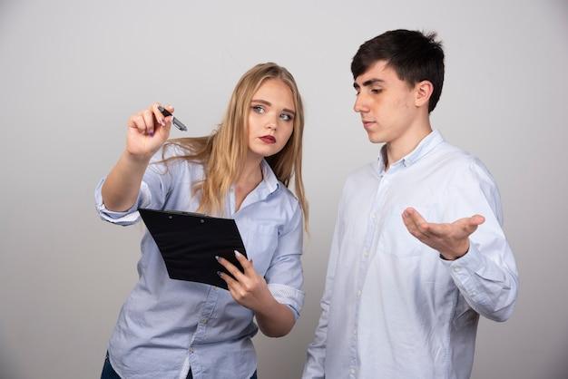 Deux jeunes collègues de bureau discutent d'un projet sur un mur gris.