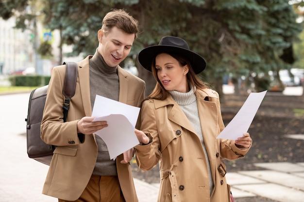 Deux jeunes collègues confiants dans des vêtements décontractés intelligents lisant des documents et en discutant tout en se déplaçant le long de la route dans un parc à la pause ou après le travail