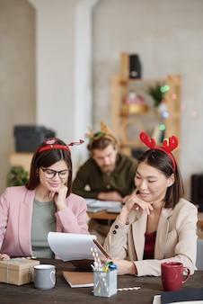 Deux jeunes collègues heureuses dans des vêtements décontractés élégants travaillant sur un rapport pour une prochaine conférence le jour de noël au bureau