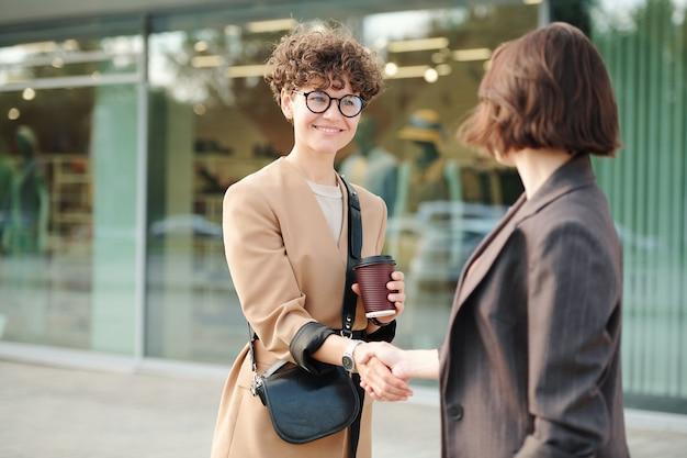 Deux jeunes collègues ou partenaires commerciaux se serrant la main après avoir négocié ou en se saluant contre l'extérieur du bâtiment