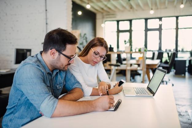 Deux jeunes collègues travaillant dans un bureau moderne à aires ouvertes.