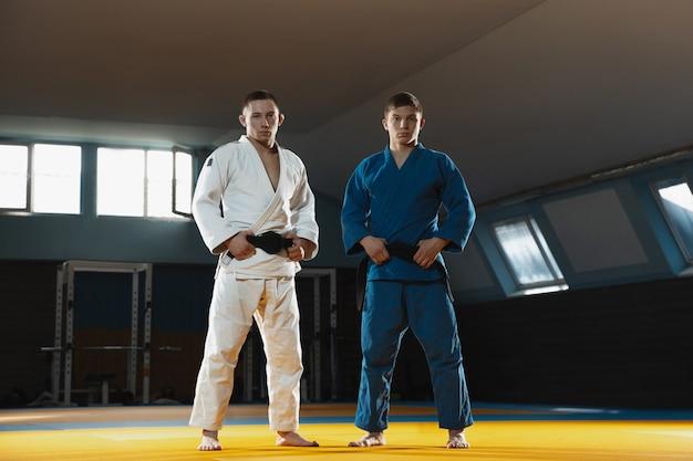 Deux jeunes combattants de judo en kimono posant confortablement dans la salle de gym forte et saine
