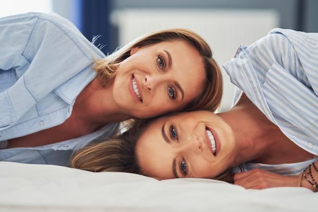 Deux jeunes copines sur le lit. photo de haute qualité