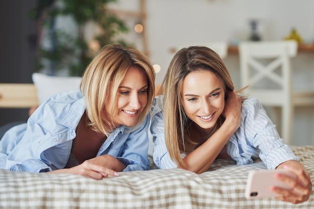 Deux jeunes copines sur le lit prenant selfie. photo de haute qualité