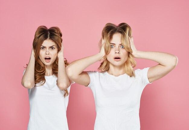 Deux jeunes copines en t-shirts blancs vue recadrée fond rose