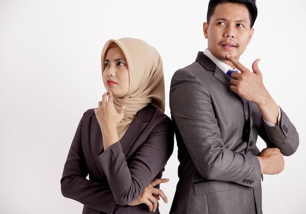 Deux jeunes couples d'affaires pensant mur blanc isolé