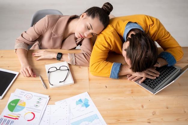 Deux jeunes courtiers épuisés sieste par bureau - homme allongé sur le clavier de l'ordinateur portable et fille endormie sur son épaule après le travail