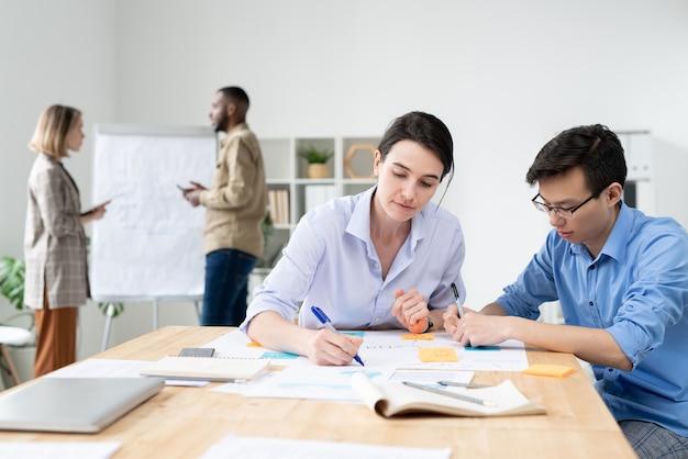 Deux jeunes courtiers interculturels assis par table au bureau et analyser des données ou prendre des notes de travail