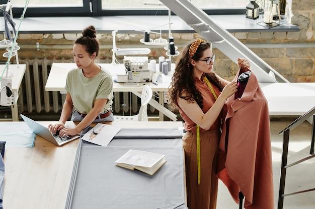 Deux jeunes créateurs de mode sérieux travaillant sur une nouvelle collection saisonnière de manteaux en studio tout en naviguant sur le net et en travaillant par mannequin