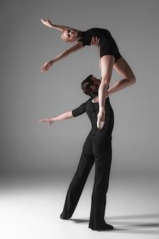 Deux jeunes danseurs de ballet moderne sur fond gris