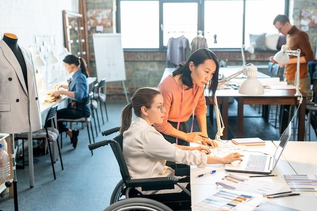 Deux jeunes designers regardant un écran d'ordinateur portable dans un environnement de travail