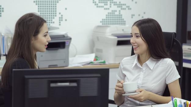 Deux jeunes employées de bureau travaillent avec des ordinateurs et parlent pendant les pauses-café