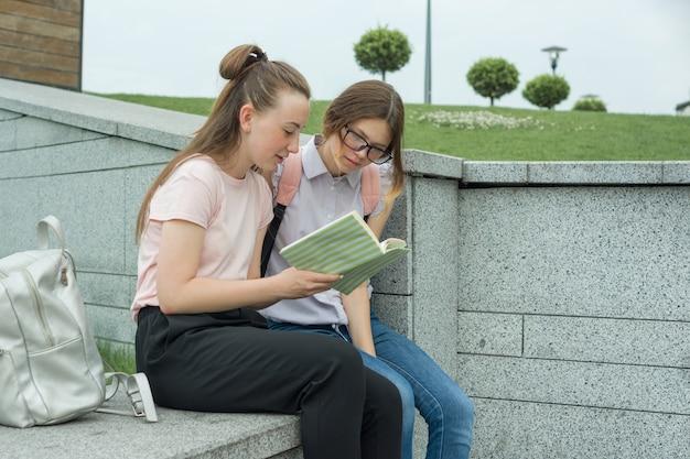 Deux jeunes étudiants de belles filles avec des sacs à dos, des livres