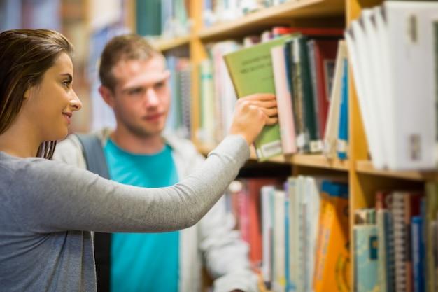 Deux jeunes étudiants sélectionnant un livre dans la bibliothèque