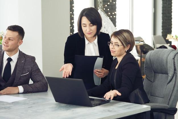 Deux jeunes femmes d'affaires au bureau, analysant des informations sur un ordinateur portable.