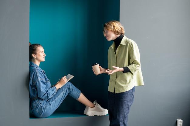 Deux jeunes femmes d'affaires contemporaines en tenue décontractée discutant du travail