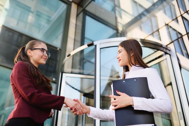 Deux jeunes femmes d'affaires mignonne se serrant la main