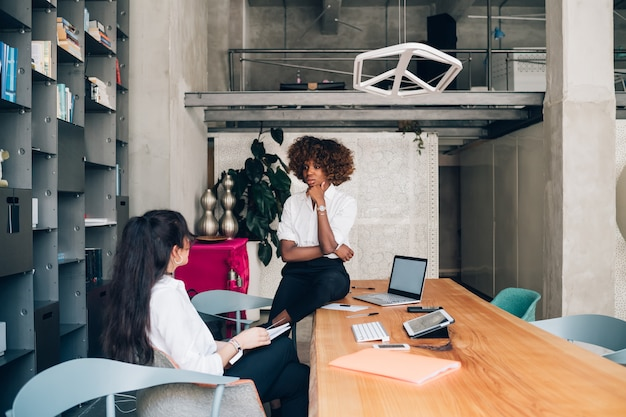 Deux jeunes femmes d'affaires multiraciales ayant une réunion dans un bureau moderne