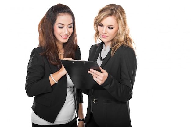 Deux jeunes femmes d'affaires avec un presse-papiers, isolé