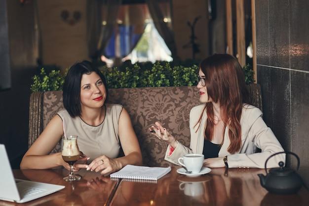 Deux jeunes femmes d'affaires souriantes avec ordinateur portable