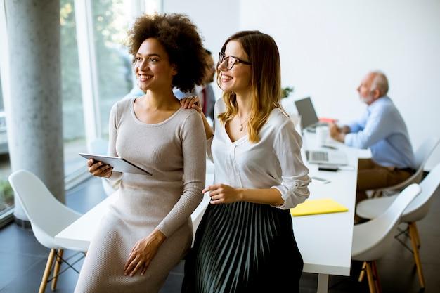 Deux jeunes femmes d'affaires avec une tablette au bureau
