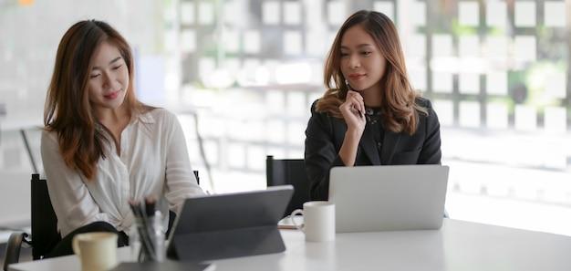 Deux jeunes femmes d'affaires travaillant ensemble sur le projet marketing