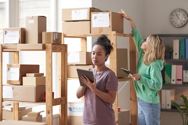 Deux jeunes femmes à l'aide de tablettes numériques tout en se tenant près du placard avec des colis travaillant en atelier