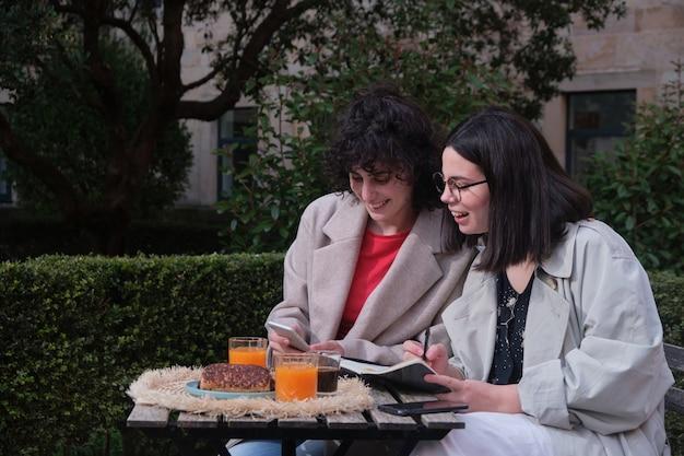 Deux jeunes femmes à l'aide d'un téléphone intelligent sur la terrasse d'un café